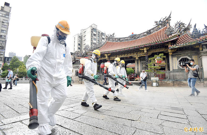 Workers spray disinfectant outside Longshan Temple in Taipei's Wanhua District yesterday. Photo: Peter Lo, Taipei Times